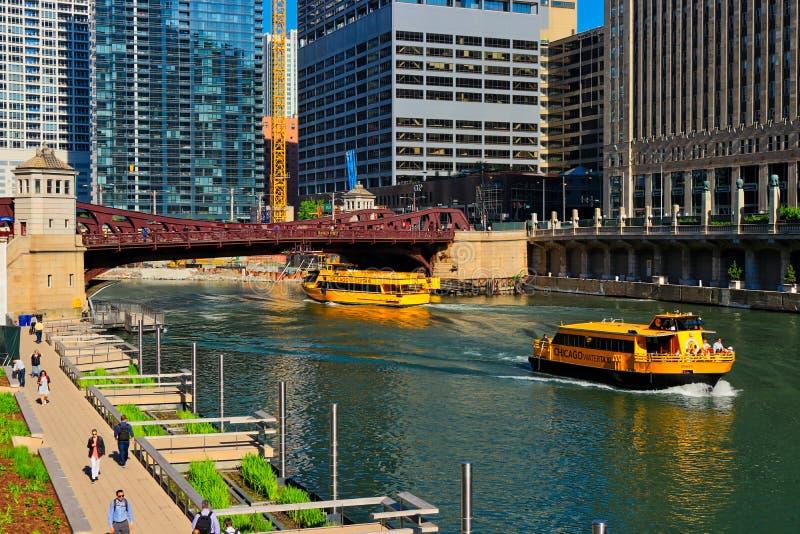 De Rivierrecreatie en gebruik van Chicago met watertaxis, en forenzen die op riverwalk op kleurrijke de lenteochtend lopen royalty-vrije stock foto's