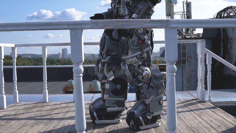 De robot beweegt zijn handen op achtergrond van stadshorizon en blauwe hemel lengte Concept technologieën met kunstmatig stock foto's