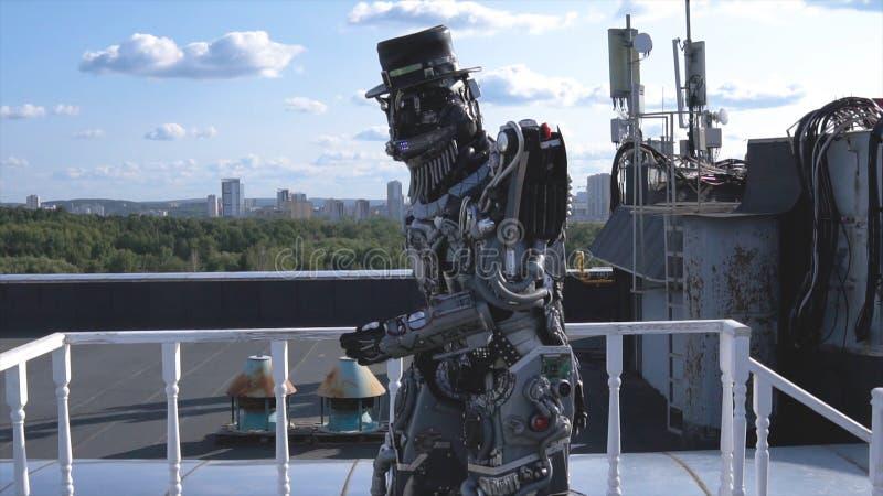 De robot beweegt zijn handen op achtergrond van stadshorizon en blauwe hemel lengte Concept technologieën met kunstmatig stock fotografie