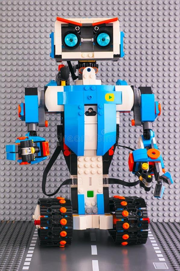 De robot die van de Legoverhoging zich op de weggrondplaat tegen grijze bas bevinden stock afbeeldingen