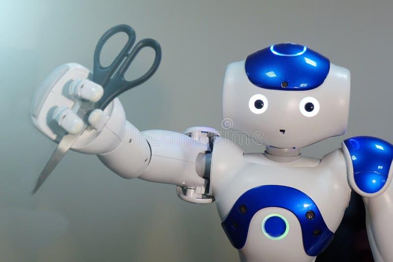 De robot houdt schaar in zijn hand kapper Een kleine robot met een menselijk gezicht en een humanoidlichaam Kunstmatige intellige royalty-vrije stock afbeelding
