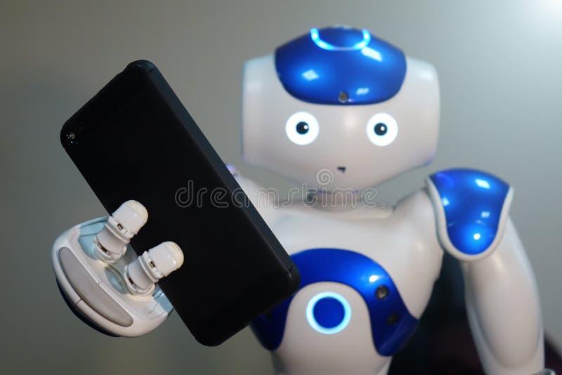 De robot houdt de telefoon in zijn hand Een kleine robot met een menselijk gezicht en een humanoidlichaam Kunstmatige intelligent royalty-vrije stock foto's