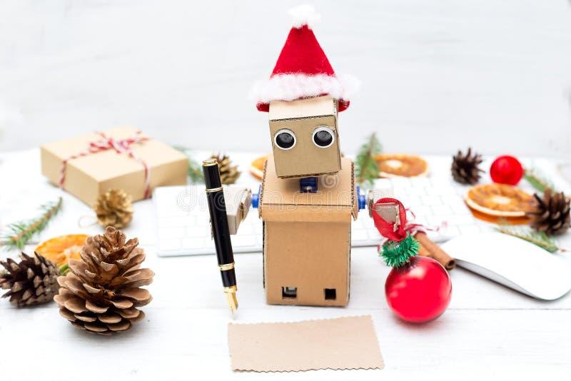 De robot schreef een kaart van de Kerstmisgroet en houdt een Kerstboom stock afbeeldingen