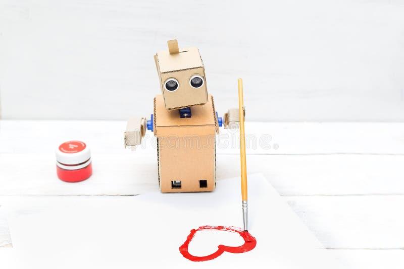 De robot trekt met een penseel en een rode verf stock foto's