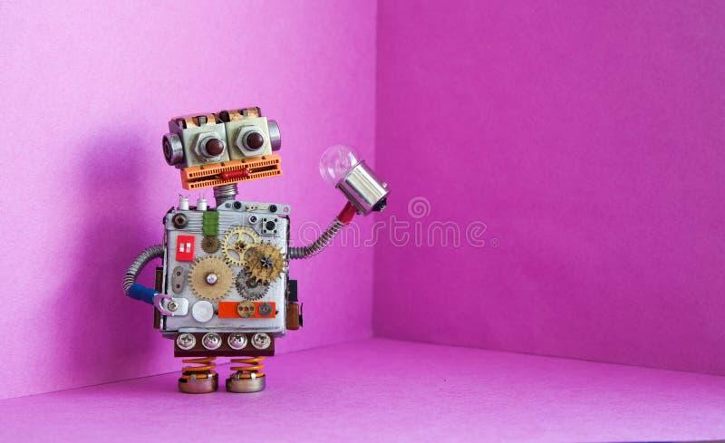 De robotelektricien houdt een gloeilamp in zijn hand Creatief ontwerp futuric robotachtig stuk speelgoed op roze achtergrond De r royalty-vrije stock foto