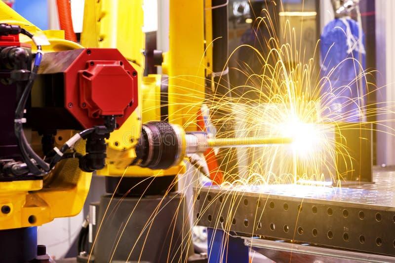 De robots van het motielassen in fabriek met vonken, productie, de industrie, fabriek stock afbeeldingen