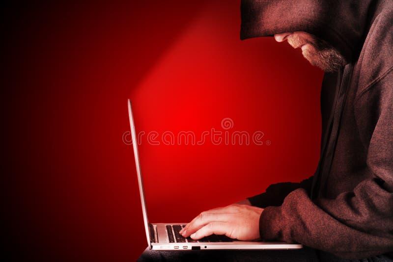 De rode achtergrond met een kap van de computerhakker stock afbeeldingen
