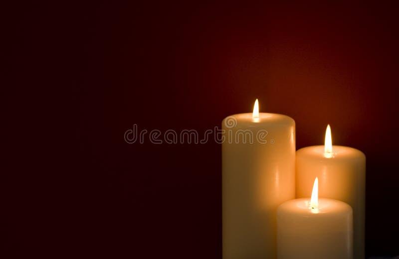 De Rode Achtergrond van drie Kaarsen stock foto's