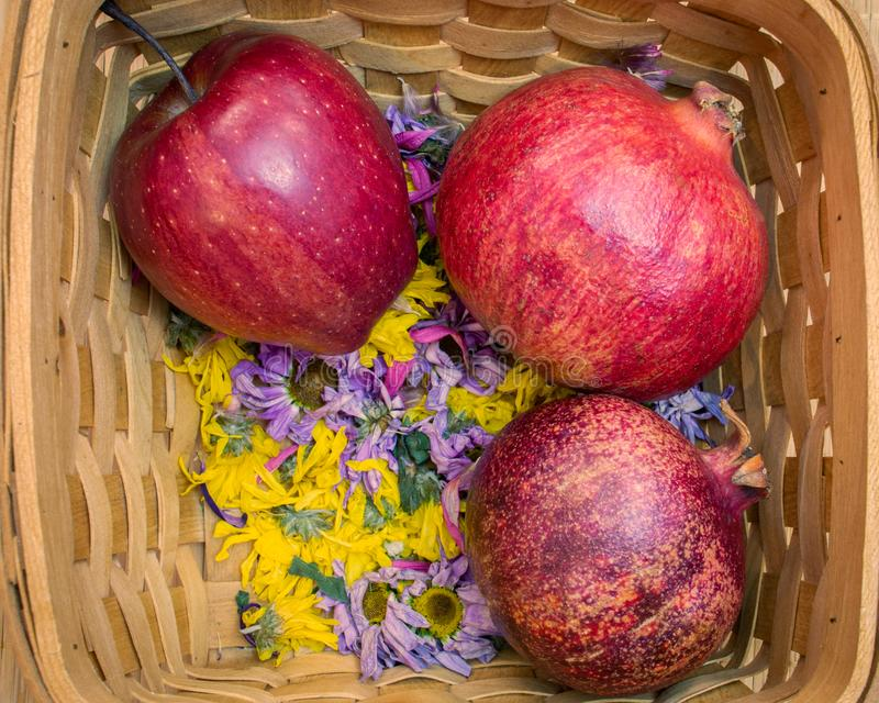 De rode appel en de granaatappels lagen in mand royalty-vrije stock afbeeldingen