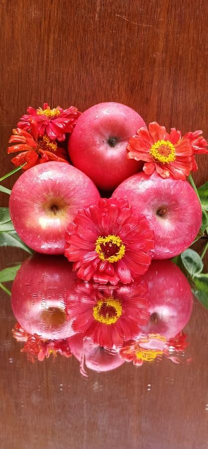 De rode appelen en het document bloeien met bruine houten achtergrond royalty-vrije stock fotografie