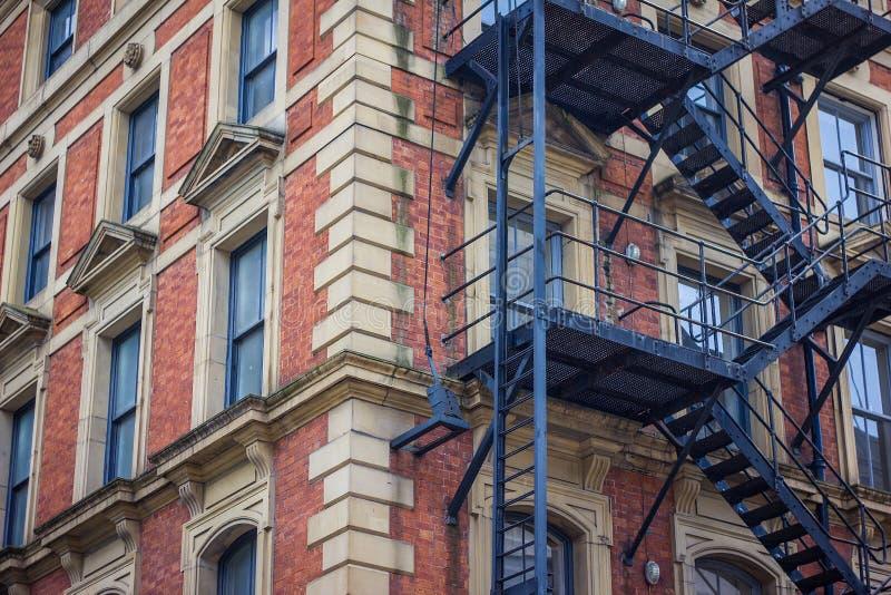 De rode bouw van het baksteenbureau met de het Bureaubouw van de metaalbrandtrap, Manchester het UK stock foto's