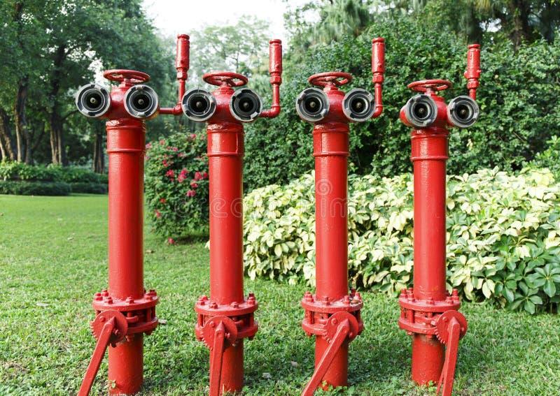 De rode brandkraan, steekt hoofdpijp, brandbeveiligingpijp voor brandbestrijding in brand en brandblus stock afbeelding