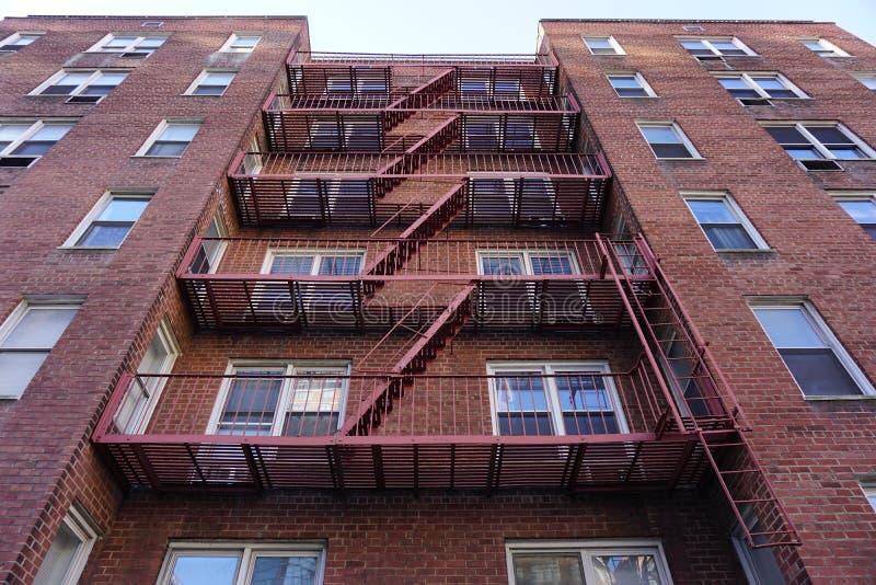 De rode Brandtrap steunt trede-de stad in steeg architectuur-staal en rode baksteenachtergrond stock afbeeldingen