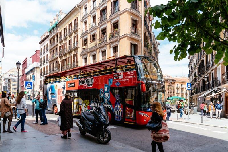 De rode bus van de stadsreis in Straat in stadscentrum van Madrid stock foto's
