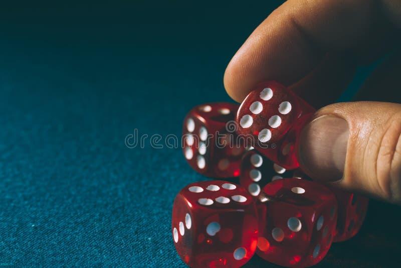 De rode close-up van hand die dobbelt met een het winnen combinatie op blauwe doek in een casino houden royalty-vrije stock foto
