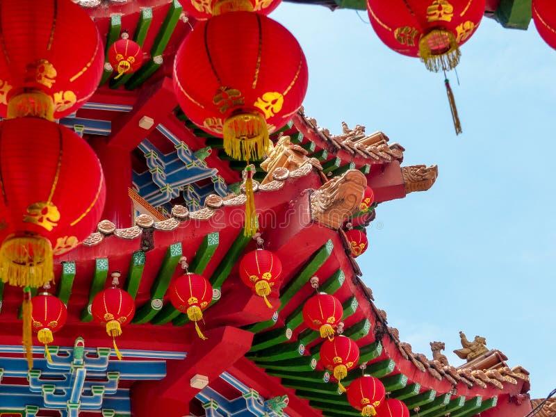 De rode details van de Lantaarndecoratie op een Chinees Tempeldak tegen een blauwe hemel stock afbeeldingen