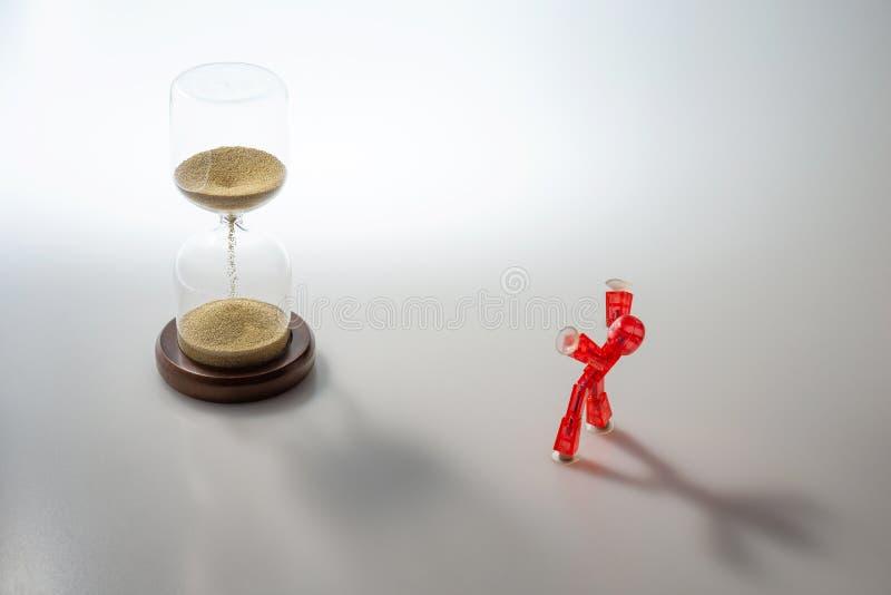 De rode die cijferwapens juichen omhoog voor tijd toe met zandloper wordt overgegaan stock foto