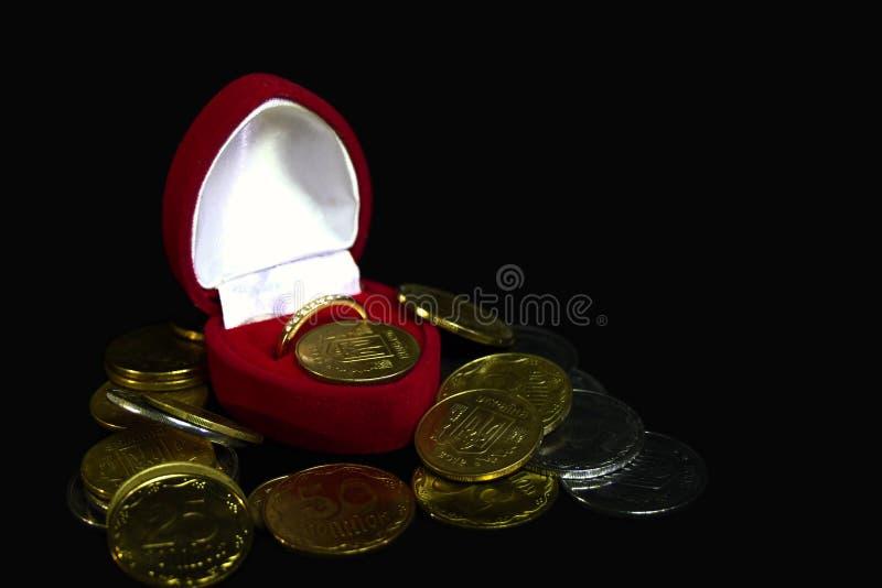 De rode doos van de fluweelgift met een gouden ring en diamanten op een zwarte achtergrond met muntstukken die van verschillende  royalty-vrije stock foto