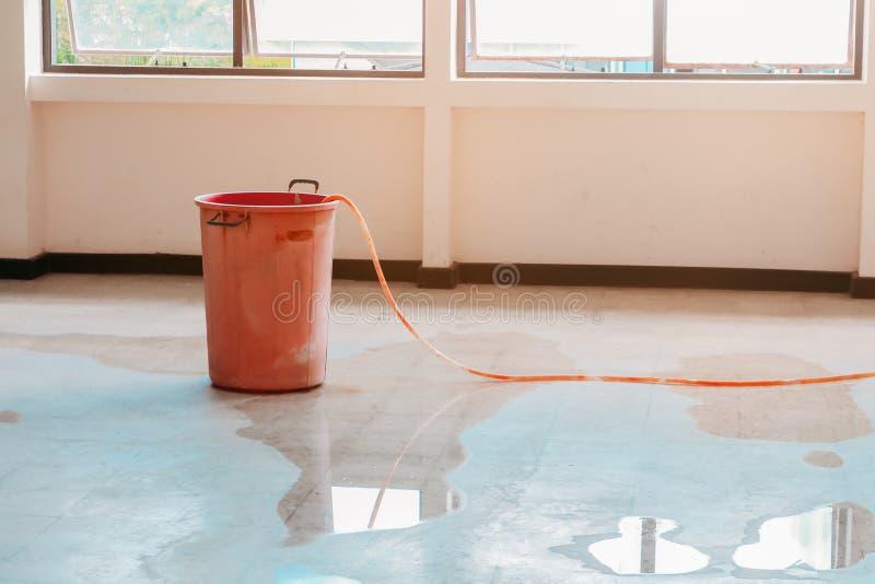 De rode emmer ligt ten grondslag binnen aan de binnenlandse het bureaubouw van het waterlek van Plafond stock foto's