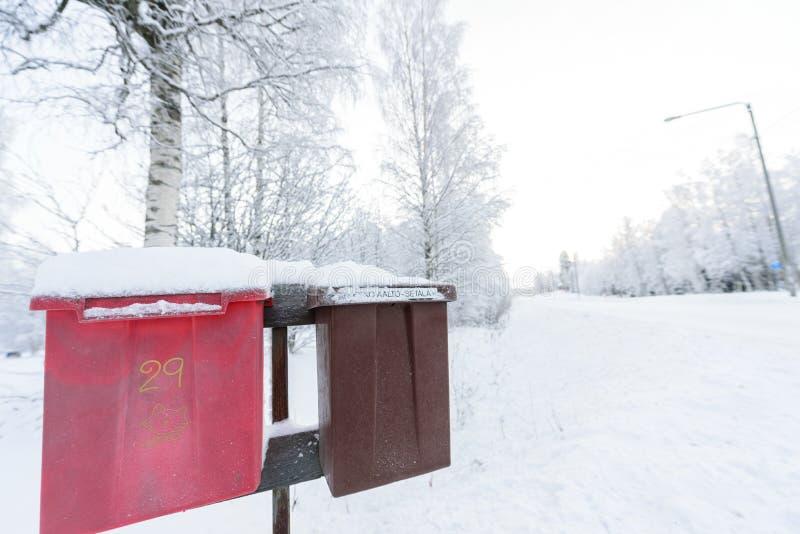 De rode en bruine brievenbus heeft met zware sneeuw in wintertijd in Lapland, Finland behandeld stock foto's