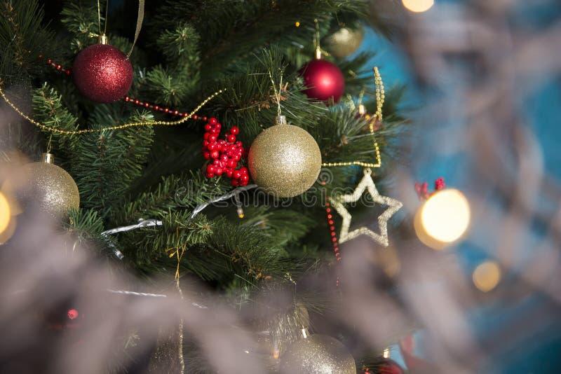 De rode en gouden gebieden hangt op de groene die pijnboom met een slinger wordt verfraaid stock afbeelding