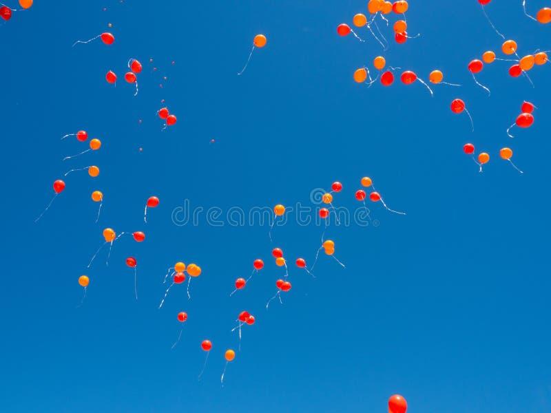 De rode en oranje ballons die met helium worden gevuld vliegen in een blauwe duidelijke hemel stock fotografie