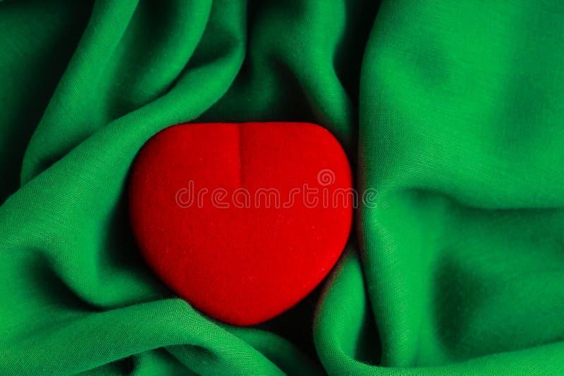 De rode gevormde gift van de juweeldoos hart huidig op groene stoffen golvende doek royalty-vrije stock afbeelding