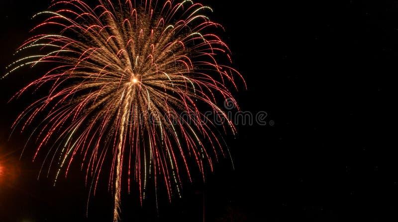 De rode, groene, en gouden explosie van het fonteinvuurwerk tegen een zwarte achtergrond op vier juli stock foto's