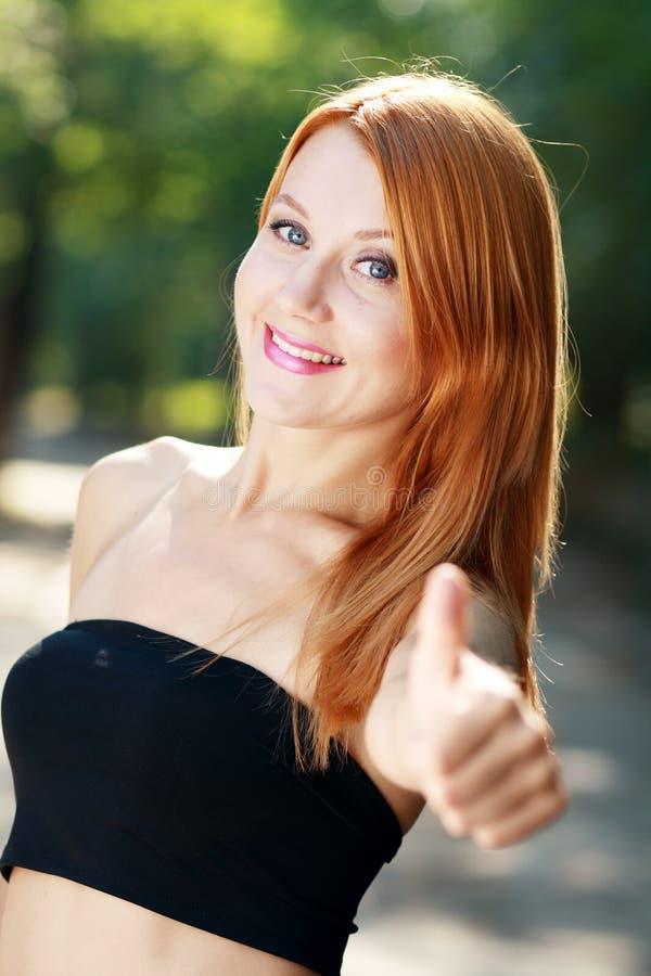 De rode haired vrouw houdt duim tegen royalty-vrije stock afbeelding