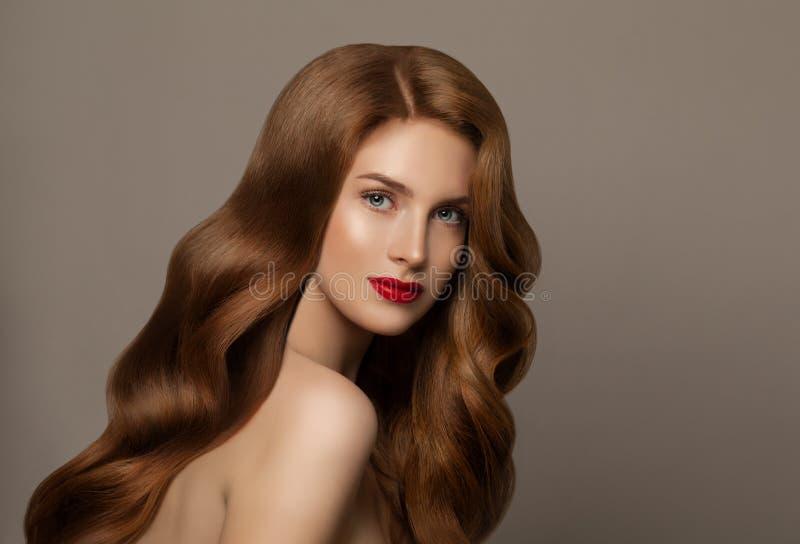 De rode haired vrouw van het portret Jong vrouwelijk model met lang krullend haar op grijze achtergrond stock afbeeldingen