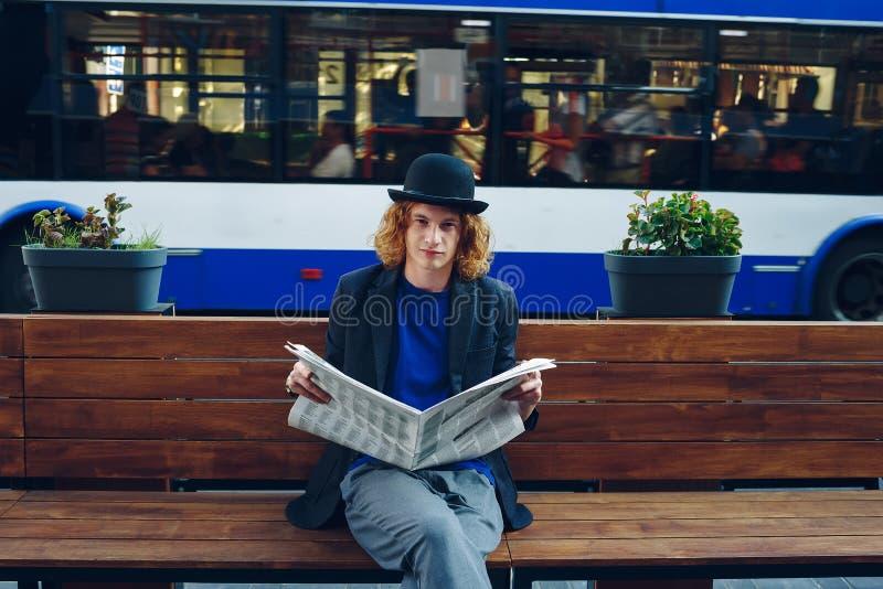 De rode haired zitting van de hipstermens op bank met krant royalty-vrije stock foto