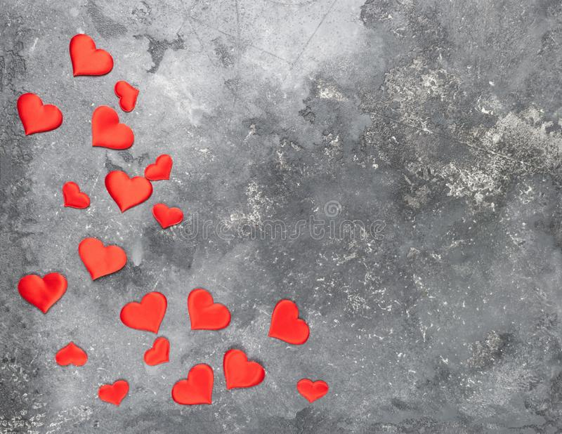 De rode harten zijn verspreid op een grijze geweven achtergrond Vlakke lay-out De ruimte van het exemplaar stock foto's