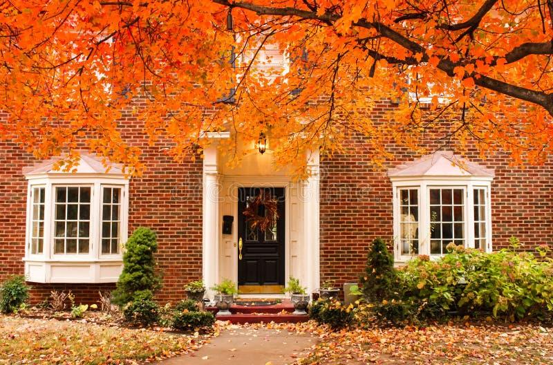 De rode ingang van het baksteenhuis met seizoengebonden kroon op deur en portiek en erkers op de herfstdag met bladeren ter plaat stock foto