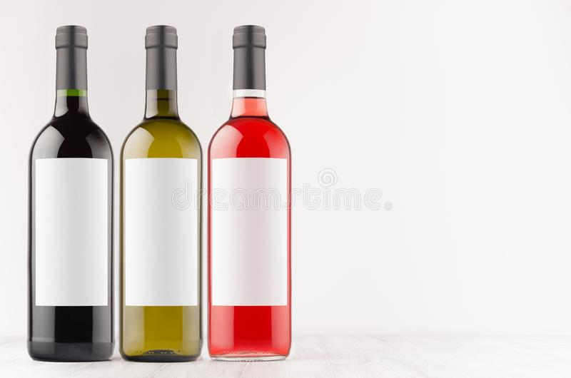 De rode inzameling van wijnflessen -, groen, zwart met lege witte omhoog etiketten op witte houten raad, spot, exemplaarruimte stock afbeeldingen