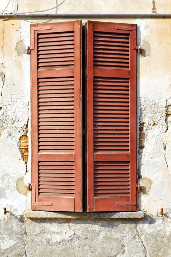 De rode jaloezie van venstervarano in de concrete baksteen stock afbeelding