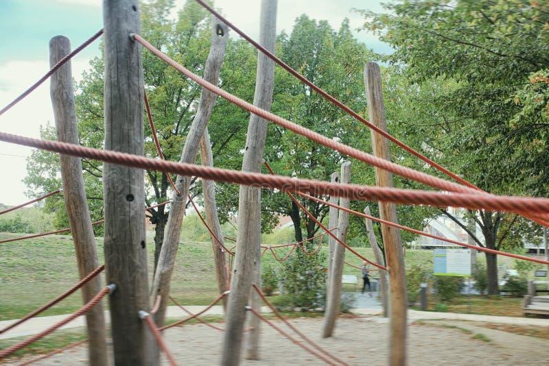 De rode jonge geitjes van Mannheim van de kabel netto houten speelplaats spelen ecozand van de pret gelukkig aard beklimmend meta stock afbeeldingen