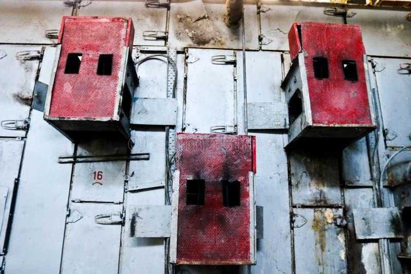 De rode kabinetten van het ijzermetaal voor geperforeerd elektrisch die netmateriaal op een muur bij een industriële petrochemisc stock foto's