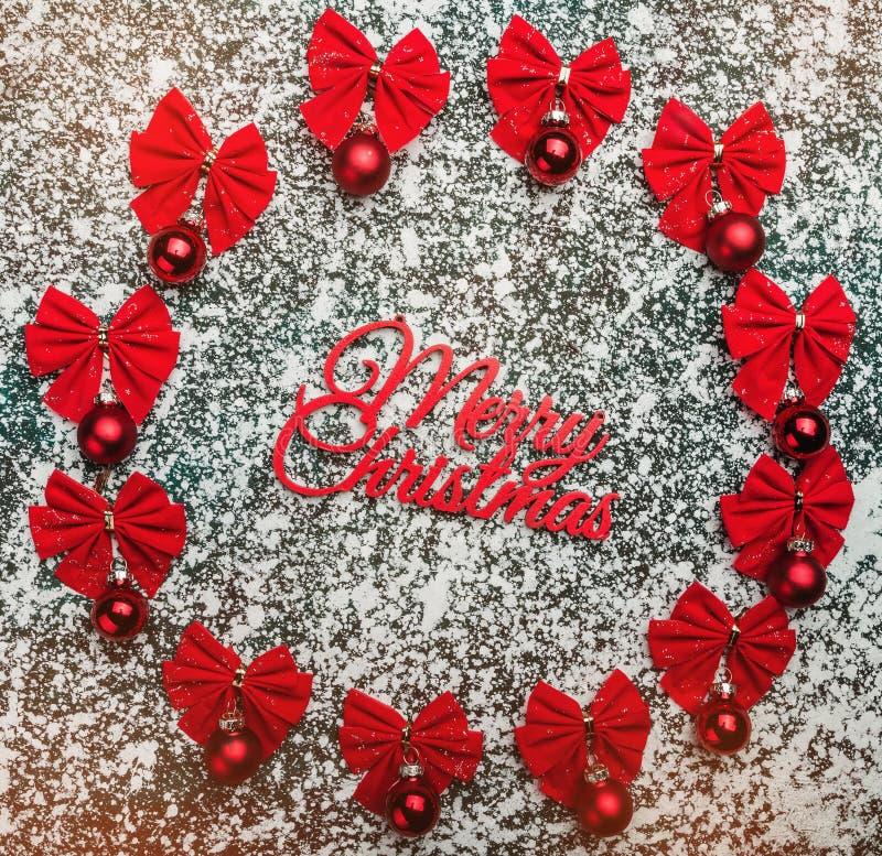 De rode Kerstmissnuisterijen met lint buigt en Vrolijk Kerstmisetiket op de winter witte achtergrond stock foto