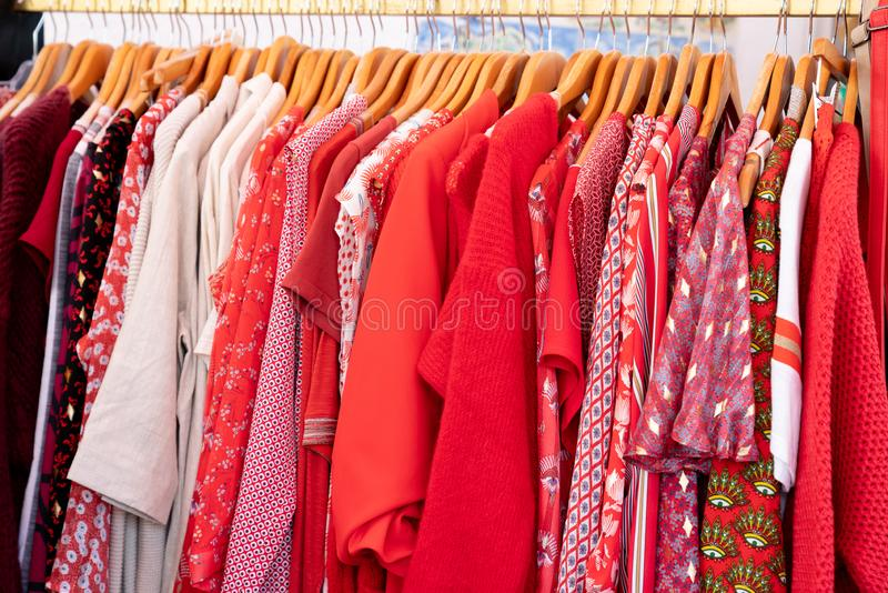 De rode kleren hangen voor verkoop in winkel Multicolored op hanger voor Zomerslijtage stock fotografie