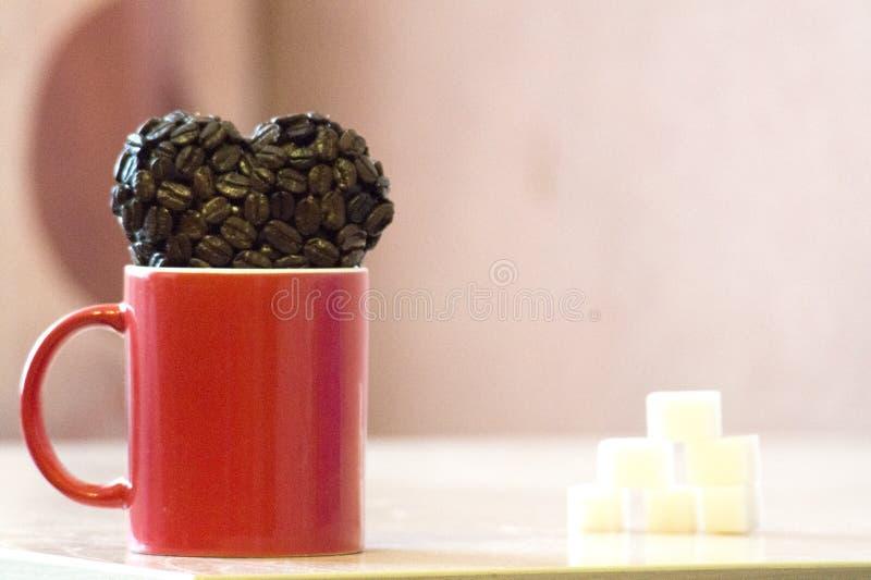 De rode mok bevindt zich op de lijst, dichtbij de mok de hartvorm van koffiebonen, een symbool van liefde royalty-vrije stock foto