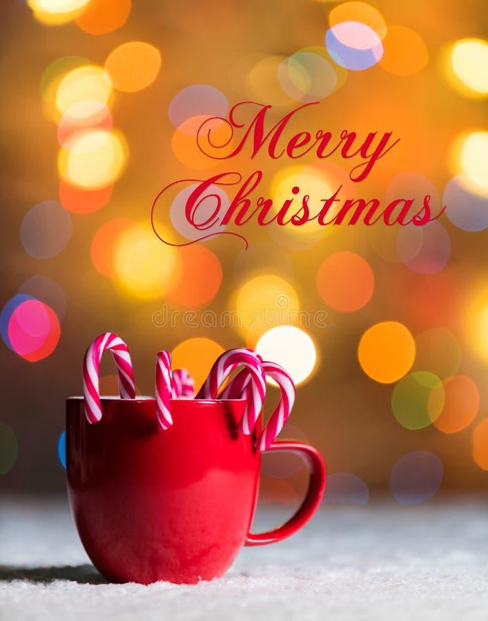 De rode mok met suikergoedriet in sneeuw met defocussed feelichten, bokeh op de achtergrond, Feestelijke Kerstmisachtergrond stock afbeeldingen