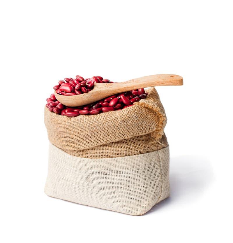 De rode nierbonen in de jutezak met houten lepel isoleren royalty-vrije stock fotografie