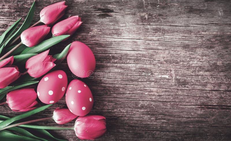 De rode paaseieren en de roze tulp bloeien hierboven op uitstekende houten lijst van royalty-vrije stock foto