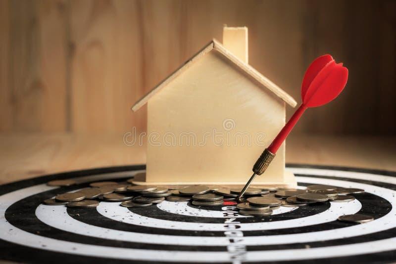 De rode pijltjepijl raakte het centrumdoel van dartboard met huis en royalty-vrije stock afbeelding