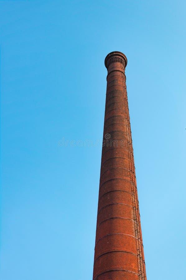 De rode pijp van de baksteenfabriek tegen blauwe hemel Het concept milieuvervuiling door schadelijke emissies in de atmosfeer royalty-vrije stock afbeeldingen