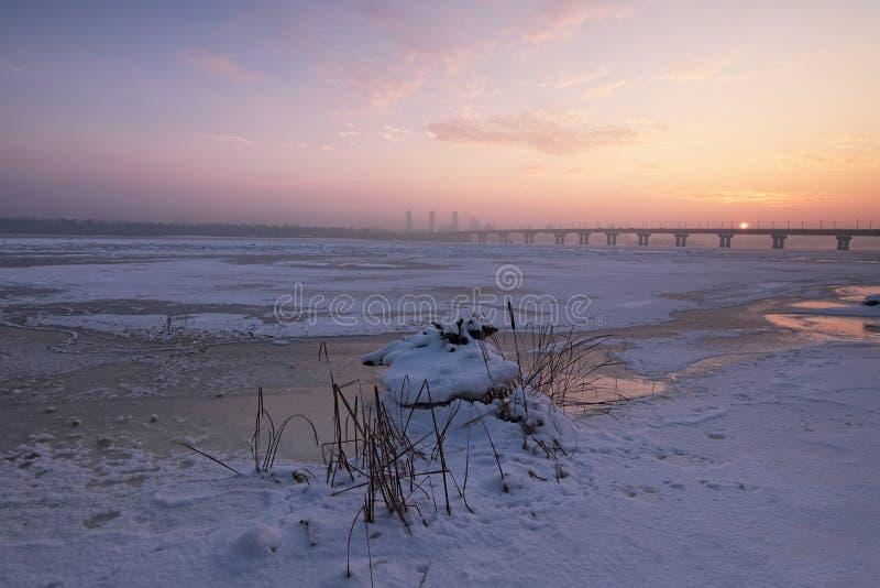 De rode schijf van de zon piept uit van achter de brug Een mooie ochtendmening van Rivier Dnipro Dnieper royalty-vrije stock foto's