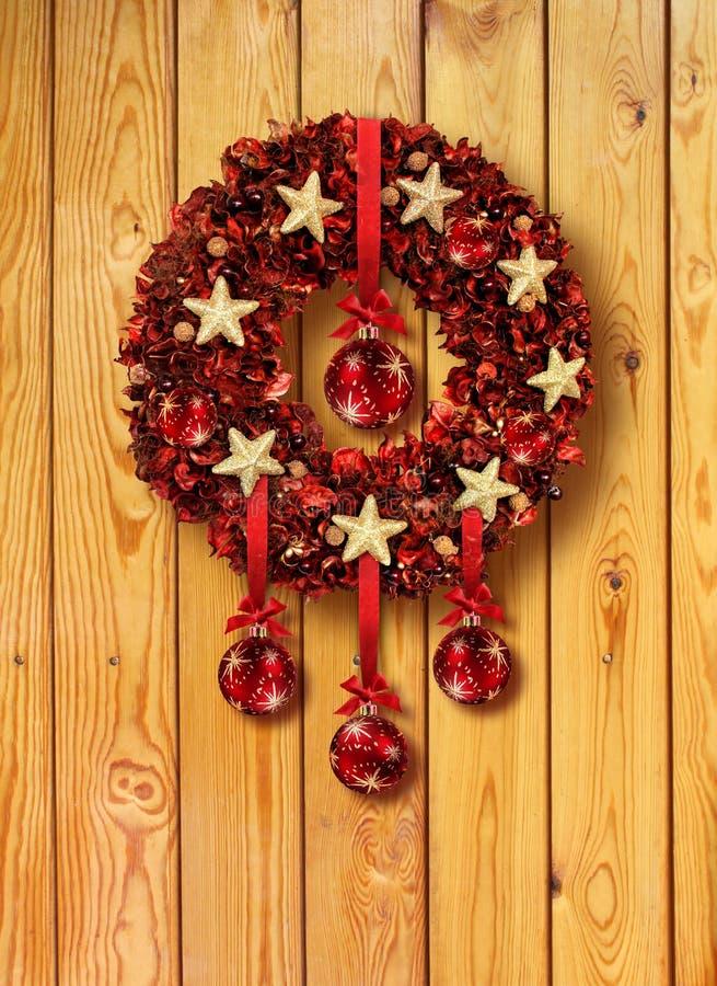 De rode slinger van Kerstmis in houten deur royalty-vrije stock foto's
