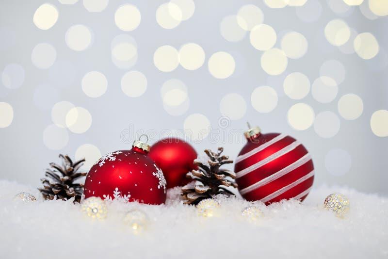 De rode snuisterijen van Kerstmis op sneeuw stock afbeelding