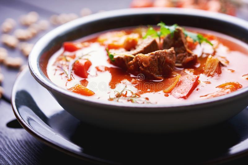 De rode soep riep borsjt met stukken vlees en kruiden op zwarte houten achtergrond Oekraïense keuken royalty-vrije stock foto