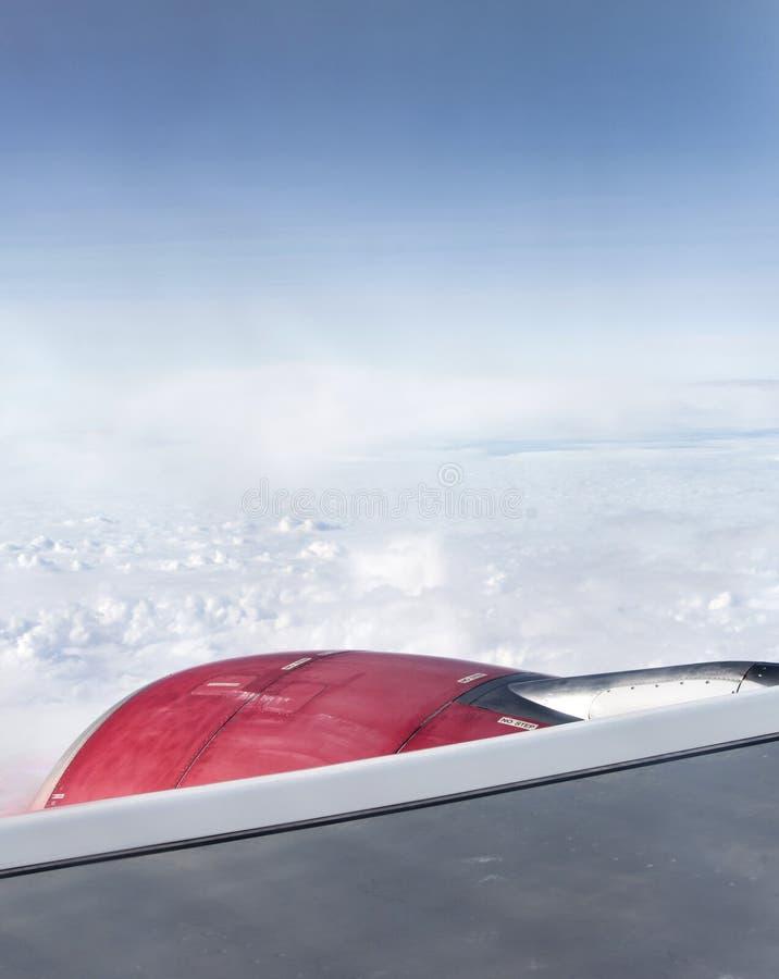 De rode straalmotorturbine kijkt door vliegtuigenvenster op de zonnige wolken van de dag blauwe hemel stock foto's